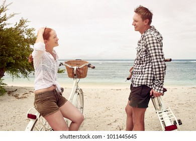 Portrait young people talking and smile while standing near their old fashioned bicycles on coast.People, leisure and lifestyle concept - happy young couple with bicycles at beach