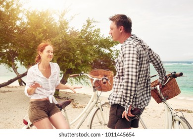 Portrait young people talking while standing near their bicycles on beach.