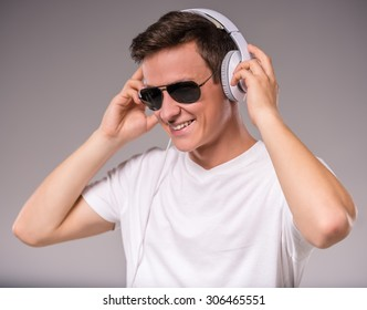 Portrait of young people use headphones on a gray background