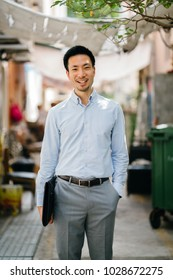 Portrait of a young and photogenic Asian Chinese man walking in a street alley in Asia. He is professionally and neatly dressed and is smiling as he walks.
