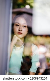 Portrait of a young and photogenic Chinese Asian woman through the reflective glass of a window of a cafe during the day. She looks thoughtful as she props her chin on her hand.