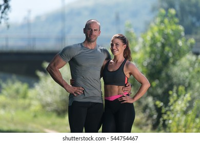 Portrait Of A Young Physically Fit Couple Showing Their Well Trained Body Resting After Running - Muscular Athletic Bodybuilder Fitness Model Posing After Exercises