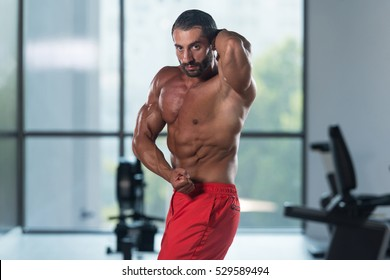 Portrait Of A Young Physically Fit Latin Man Performing Side Chest Pose - Muscular Athletic Bodybuilder Fitness Model Posing After Exercises