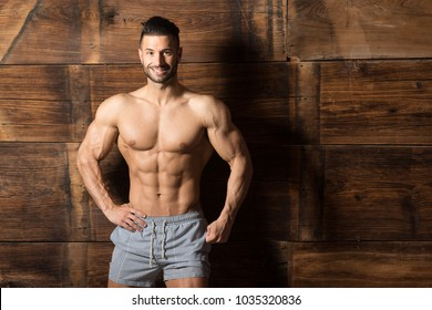 Portrait of a Young Physically Fit Man Showing His Well Trained Body While Wearing Sports Shorts - Muscular Athletic Bodybuilder Fitness Model Posing After Exercises on Wooden Wall