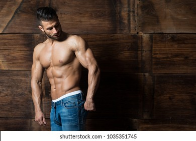 Portrait of a Young Physically Fit Man Showing His Well Trained Body While Wearing Blue Jeans - Muscular Athletic Bodybuilder Fitness Model Posing After Exercises on Wooden Wall