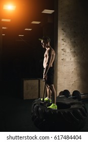 Portrait Of A Young Physically Fit Man Workout At Gym With Hammer - Muscular Athletic Bodybuilder Fitness Model Posing After Exercises On Tractor Tire