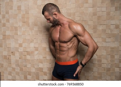 Portrait of a Young Physically Fit Man Showing His Well Trained Body - Muscular Athletic Bodybuilder Fitness Model Posing After Exercises on Wall Near the Wall - a Place for Your Text