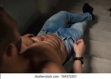 Portrait of a Young Physically Fit Man Showing His Well Trained Body On Stairs - Muscular Athletic Bodybuilder Fitness Model Posing After Exercises on Wall Near the Wall - a Place for Your Text