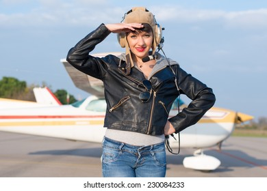 Portrait of young pilot against airplane
