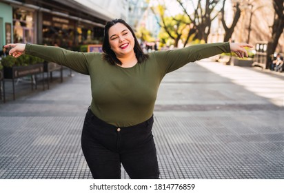 Portrait of young plus size woman smiling while standing outdoors at the street. Urban concept.