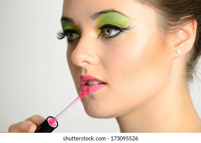 Portrait of young Polish female. Teenage girl with colorful makeup using lip gloss on her lips.