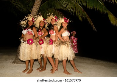Portrait of young Polynesian Pacific Island Tahitian women dance group in a colorful costume dancing on tropical beach in Aitutaki, Cook Islands. Real people. Copy space