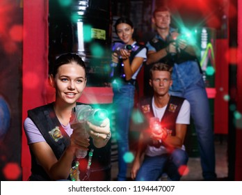 Portrait of young positive cheerful glad smiling girl took aim colored laser guns during laser tag game in labyrinth
