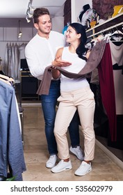 Portrait of young positive couple pick out jeans at clothing shop. Focus on man