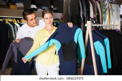 Portrait of young positive couple shopping together, searching new wetsuits for surf at store. Focus on man