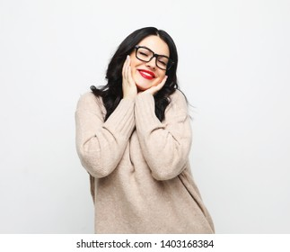 Portrait of young positive female with cheerful expression, dressed in casual clothes, over white background.