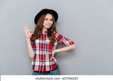 Portrait of a young positive girl in plaid shirt showing ok gesture and winking isolated over gray background