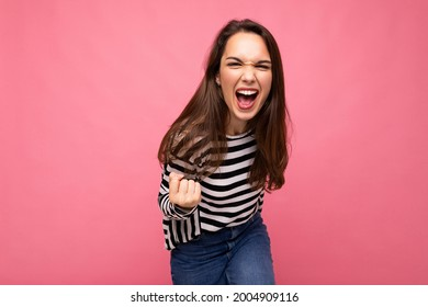Portrait of young positive happy beautiful brunet female person with sincere emotions wearing casual striped pullover isolated on pink background with empty space and celebrating winning shouting yes - Shutterstock ID 2004909116
