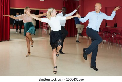 Portrait of young positive people dancing twist in pairs at dance hall