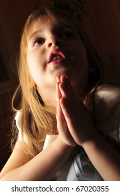 Portrait of young praying girl sitting in comfortable armchair in dark room with lightning lantern