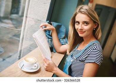 Portrait of a young pregnant girl who is sitting in a cafe reading a magazine and drinking coffee with a croissant during your vacation