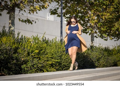 portrait of young pregnant lady with bege coat walking on the street