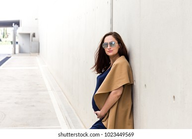 portrait of young pregnant lady with sunglasses posing near concrete wall