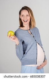 portrait of young pregnant woman posing with apple in studio  isolated on grey