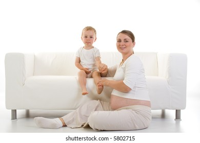 Portrait of a young pregnant woman with a toddler...predominant color is white.