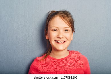 Portrait of young preteen 9-10 year old girl wearing pink top, standing against blue purple background