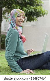 Portrait young pretty Asian muslim college girl with laptop and smile