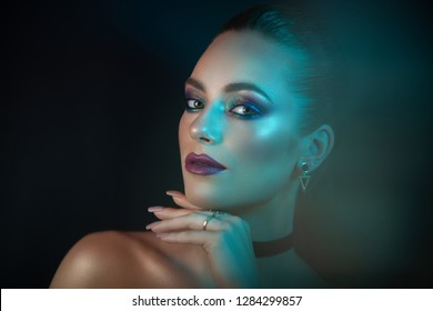 Portrait of a young, pretty and attractive girl with expressive facial features and bright make-up. A girl poses in on camera, showing off her image on a dark background.