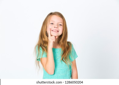 portrait of young pretty blonde girl thinking in front of white background