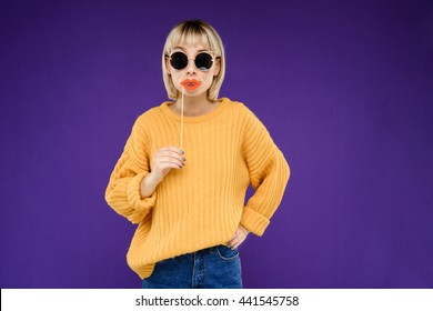 Portrait of young pretty blonde girl in yellow sweater and jeans wearing fake lips over purple background.