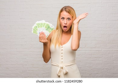 Portrait of young pretty blonde woman against a bricks wall crazy and desperate, screaming out of control, funny lunatic expressing freedom and wild. Holding euro banknotes.