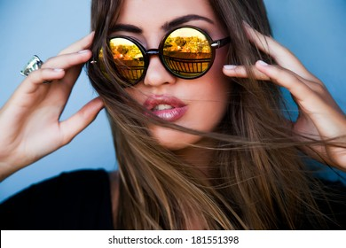Portrait of young pretty brunette model in cool mirror stylish sunglasses, fashion style and make up.