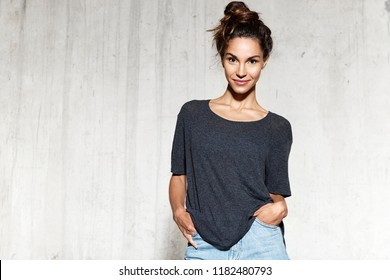 Portrait of young pretty brunette woman posing in mock-up shirt and jean shorts. Beautiful smiling girl indoors isolated on cement background. Copy space in left side