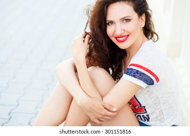 Portrait of young pretty brunette woman in the city in summertime. Close portrait.