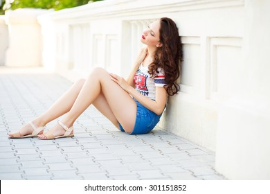 Portrait of young pretty brunette woman with curly hair and red lips in the city in summertime. Pretty girl wearing shorts, t-short and sandals sitting on the city street and resting with close eyes.