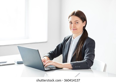 Portrait of young pretty business woman with laptop in the office