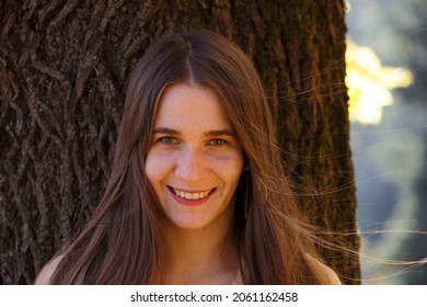 Portrait of a young pretty Caucasian girl with troubled skin wearing a beige coat against a thick tree in autumn.