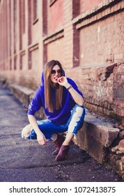Portrait of young pretty funny smiling girl in blue clothes. Young happy woman having fun outdoor