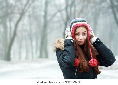 Portrait of young pretty funny smiling girl in cold weather dressed in color clothes and warm hat. Young happy woman having fun outdoor. Copyspace