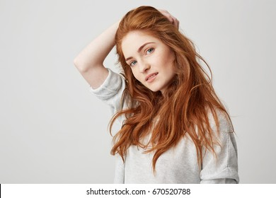 Portrait of young pretty ginger girl with freckles looking at camera smiling touching hair over white background.