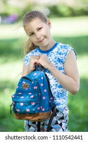 Portrait of young pretty girl cuddles bag to body, stands in summer park