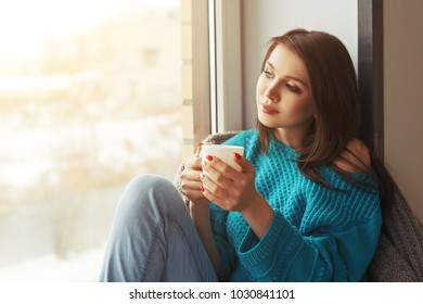 portrait of a young pretty girl with a Cup of coffee in her hands dreaming looking out the window