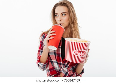 Portrait of a young pretty girl in plaid shirt holding popcorn and drinking from a plastic cup isolated over white background