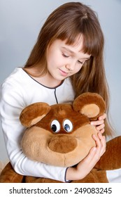 A portrait of a young pretty girl smiling and hugging her teddy bear