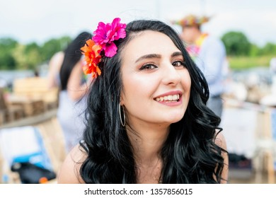 Portrait of young pretty happy woman with flower in her hair. Party, Fun and colorful.