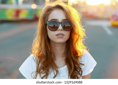 Portrait of a young pretty hipster woman's face in stylish sunglasses with red curly hair in a stylish T-shirt on the background of bright orange summer sun. Stylish girl enjoying the summer sunlight.